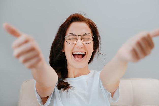 Mulher jovem com óculos closeup está feliz com um trabalho perfeitamente executado, mostrando os polegares desfocados para cima.