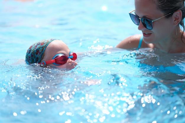 Mulher jovem com óculos de sol ensinando criança a nadar na piscina