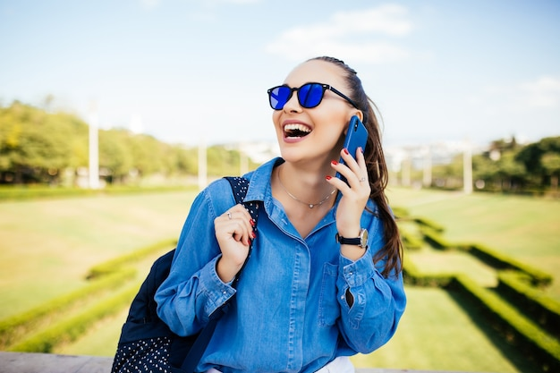 Mulher jovem com óculos de sol falando em um celular contra um fundo de planta