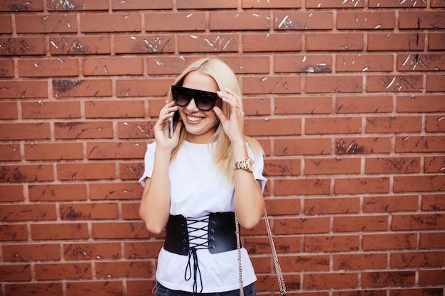 Mulher jovem com óculos de sol rindo enquanto fala no celular ao lado de uma parede de tijolos marrons ao ar livre em um dia ensolarado