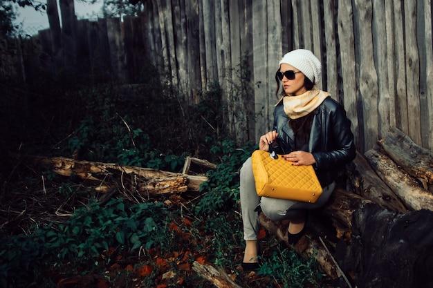 Mulher jovem com óculos de sol sentada perto de um velho celeiro tarde da noite