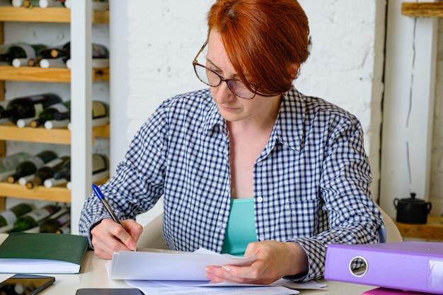 Mulher jovem com óculos e cabelo curto ruivo trabalhando com documentos na mesa