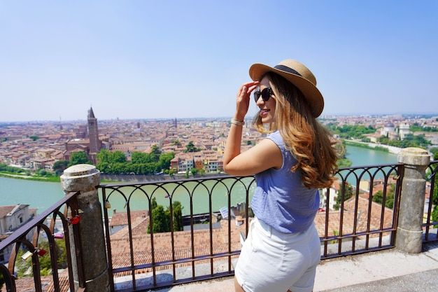 Mulher jovem com óculos escuros e chapéu se vira no terraço panorâmico em verona, itália