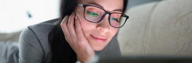 Mulher jovem com óculos está deitada no sofá e olhando para o tablet em casa, lendo livros no