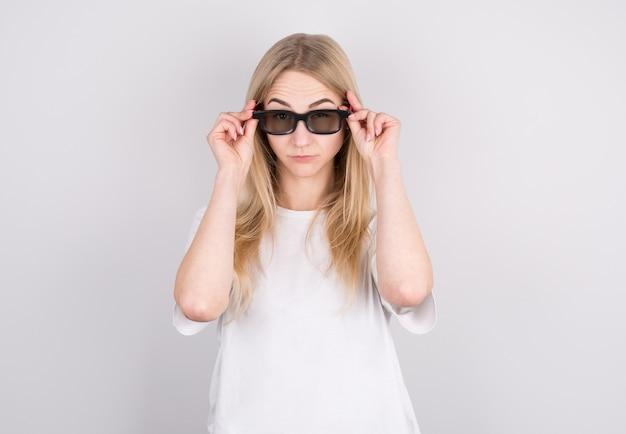 Mulher jovem com óculos está muito surpresa olhando e baixando os óculos. surpresa e conceito de compra em fundo branco.