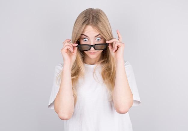 Mulher jovem com óculos fica muito surpresa olhando para baixo e baixando os óculos. surpresa e conceito de compra em fundo branco.