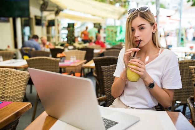 Mulher jovem com óculos na cabeça sorrindo alegremente, descansando em um café e navegando na internet usando um laptop