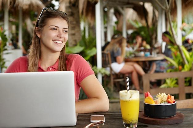 Mulher jovem com óculos na cabeça sorrindo alegremente, descansando no café e navegando na internet usando um laptop, sentada à mesa com batido de frutas e telefone celular, pessoas almoçando