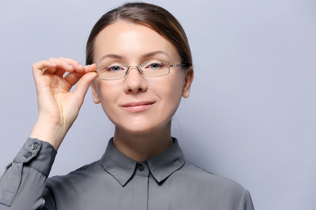 Mulher jovem com óculos na superfície cinza