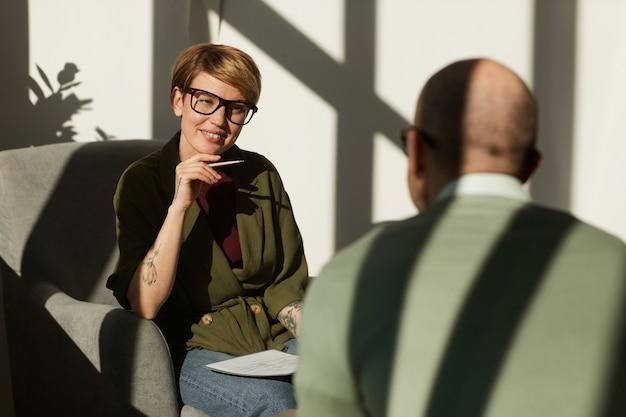 Mulher jovem com óculos, sentada na poltrona e conversando com o homem que vai dar uma entrevista no escritório