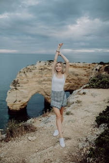 Mulher jovem com os braços abertos em pé sobre uma rocha em frente a uma praia oceânica em portugal