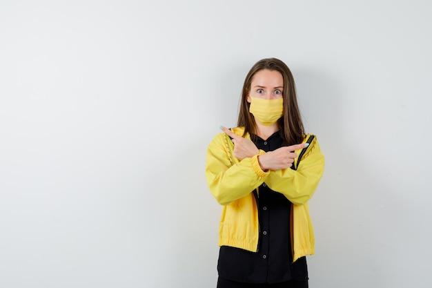 Mulher jovem com os braços cruzados e apontando para direções opostas com o dedo indicador