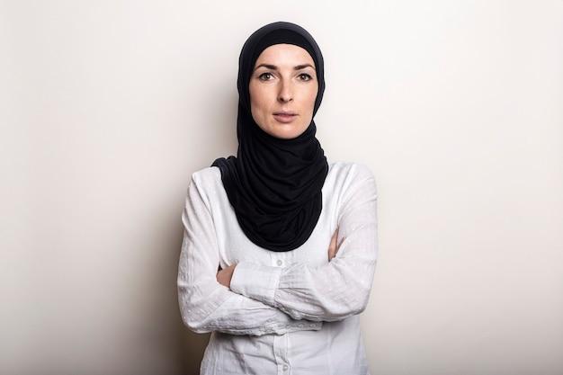 Mulher jovem com os braços cruzados vestida com camisa branca e hijab