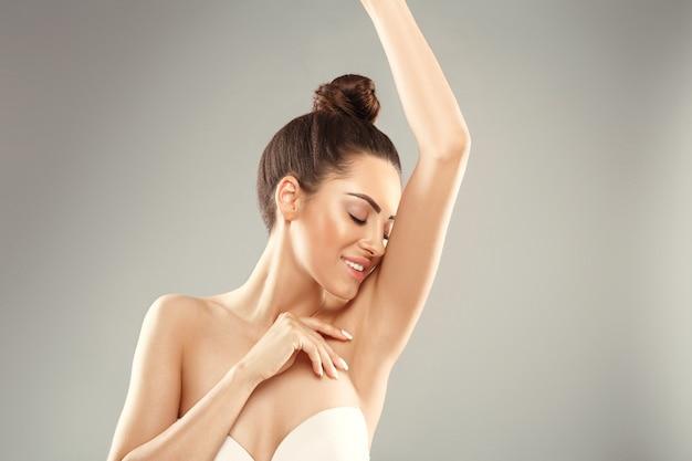 Mulher jovem com os braços erguidos e as axilas limpas