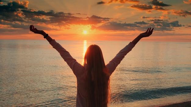 Mulher jovem com os braços estendidos, apreciando a beleza do pôr do sol no guindaste do mar, atirou