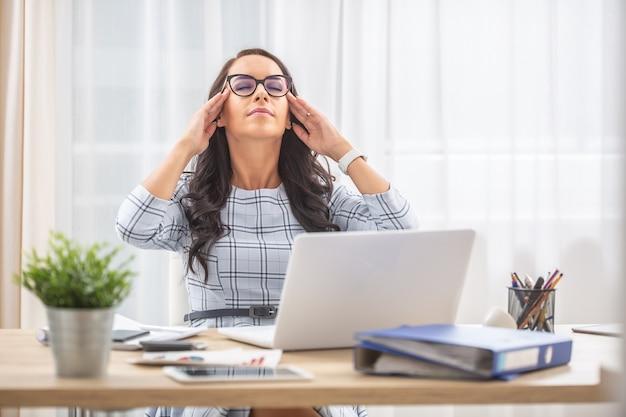 Mulher jovem com os olhos fechados, os dedos nas têmporas, recuperando a energia mental em seu equilíbrio entre vida profissional e pessoal.