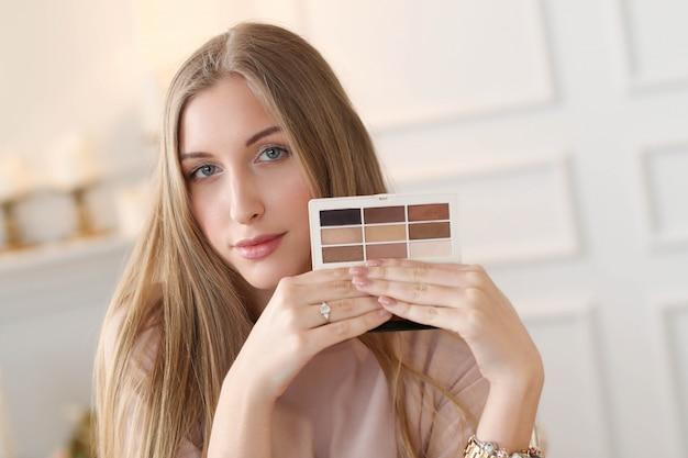 Mulher jovem com paleta de cores para maquiagem