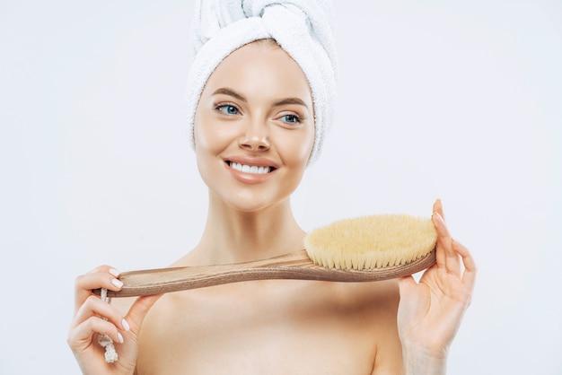 Mulher jovem com pele fresca e saudável, usa escova corporal, sorri suavemente, usa toalha de banho na cabeça, posa em topless, isolada sobre fundo branco. acessórios de spa. mulheres, cuidados com o corpo, conceito de higiene