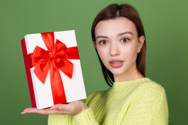 Mulher jovem com pele natural limpa e perfeita e lábios grandes marrons maquiados na parede verde segurando uma caixa de presente feliz e animada