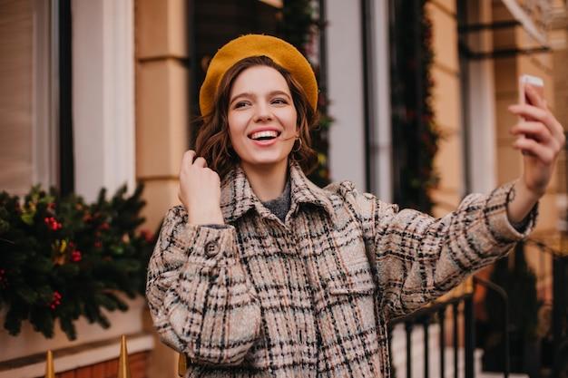 Mulher jovem com pele perfeita sorrindo enquanto tira uma selfie