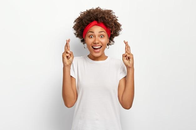 Mulher jovem com penteado afro, cruza os dedos para dar sorte, espera que os milagres aconteçam, usa bandana vermelha e camiseta casual