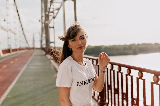 Mulher jovem com penteado comprido e camiseta branca vestida está caminhando pela cidade retrato ao ar livre de mulher passando seu tempo de lazer
