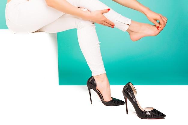 Mulher jovem com pernas magras, sentindo dores por usar sapatos de salto altos. closeup jovem massageando os dedos dos pés sobre fundo azul. conceito de saúde e médico.