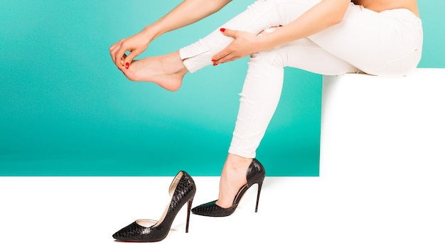 Mulher jovem com pernas magras, sentindo dores por usar sapatos de salto altos.