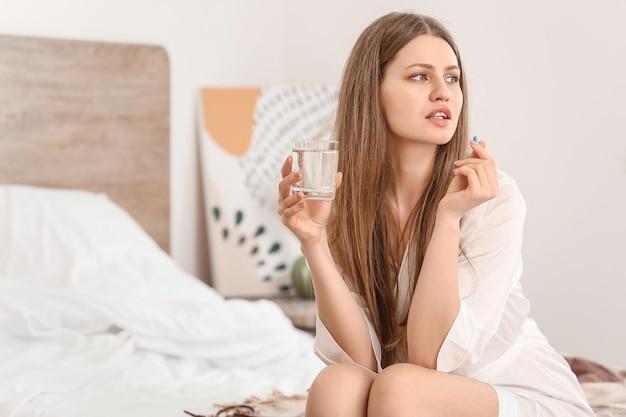 Mulher jovem com pílulas anticoncepcionais no quarto