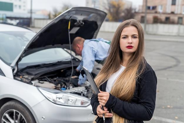 Mulher jovem com prancheta e trabalhador consertando carro