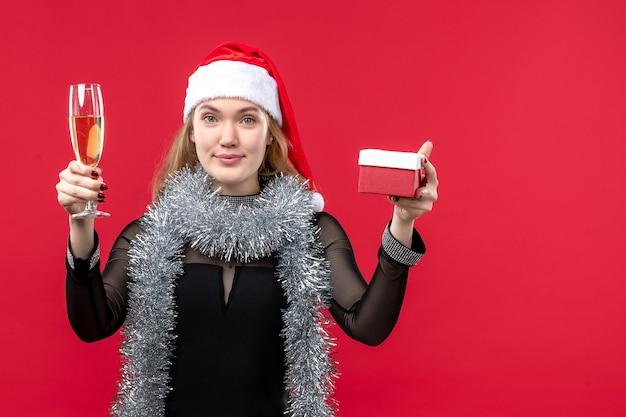 Mulher jovem com presente comemorando na parede vermelha feriado cor natal