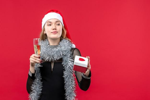 Mulher jovem com presente comemorando na parede vermelha férias de natal