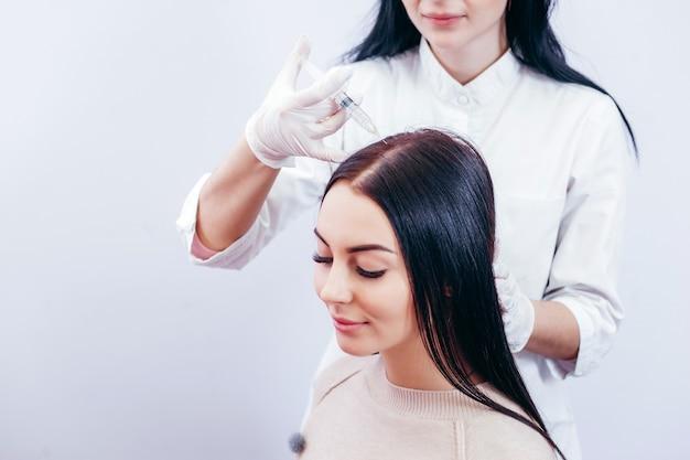 Mulher jovem com problema de queda de cabelo recebendo injeção, close-up