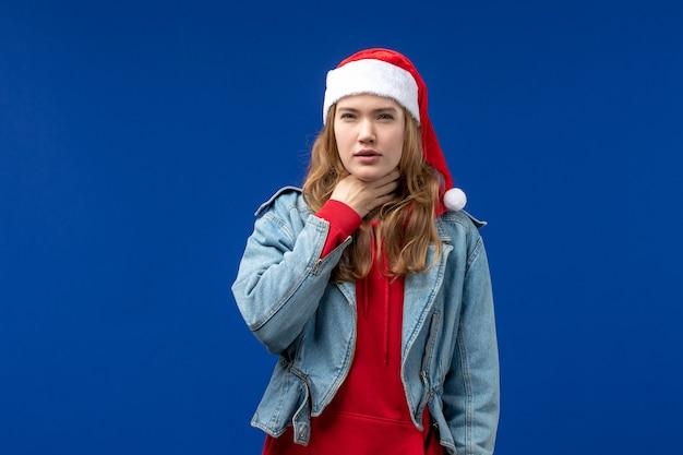 Mulher jovem com problemas de garganta na cor de fundo azul da emoção do natal de frente