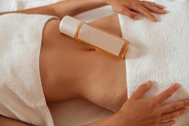 Mulher jovem com produto cosmético na barriga, descansando em salão de spa