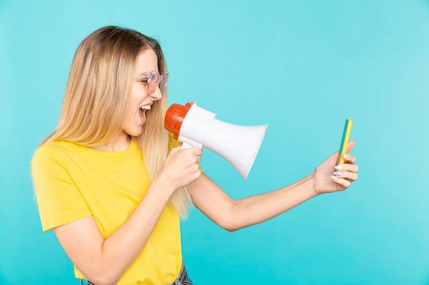 Mulher jovem com raiva gritando com o megafone para o celular no azul