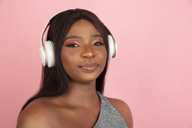 Mulher jovem com retrato de fones de ouvido na parede rosa do estúdio