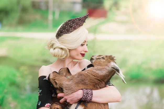 Mulher jovem com rosto lindo e cabelo loiro encaracolado em um vestido folclórico segurando um cordeirinho branco fofo