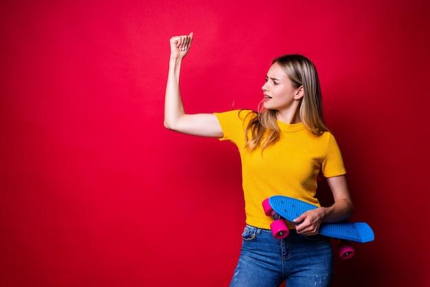 Mulher jovem com roupa casual segurando um skate, mostrando os bíceps, em pé contra a parede vermelha