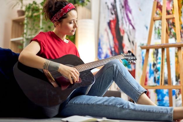 Mulher jovem com roupa casual tocando violão enquanto estuda música em casa