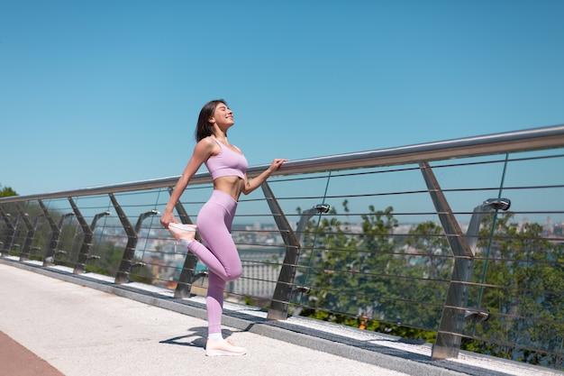 Mulher jovem com roupa esportiva adequada na ponte em uma manhã quente de sol se espreguiçando