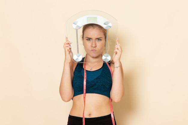 Mulher jovem com roupa esportiva segurando balanças na mesa branca, vista frontal, beleza, beleza, corpo, saúde, exercício