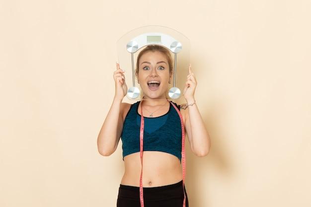 Mulher jovem com roupa esportiva segurando escalas na parede branca de frente, corpo, esporte, beleza, saúde, exercícios