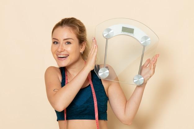 Mulher jovem com roupa esportiva segurando escalas na parede branca, vista frontal, corpo, esporte, beleza, saúde