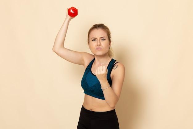 Mulher jovem com roupa esportiva segurando halteres vermelhos na parede branca de frente para esporte, corpo, saúde, beleza, vista frontal