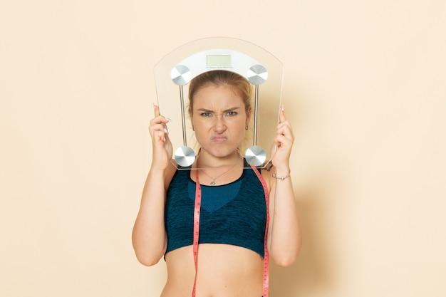 Mulher jovem com roupa esportiva, segurando uma balança na parede branca, vista frontal, ajuste, beleza, exercícios, saúde, corpo