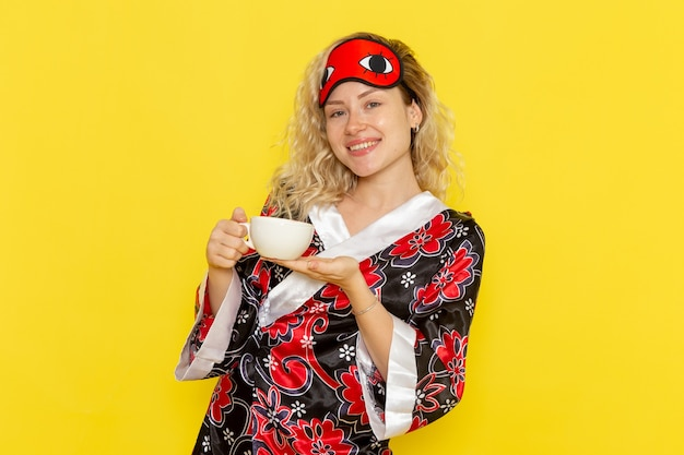 Mulher jovem com roupão de noite e máscara de olho se preparando para dormir segurando uma xícara de café, sorrindo na mesa amarela.