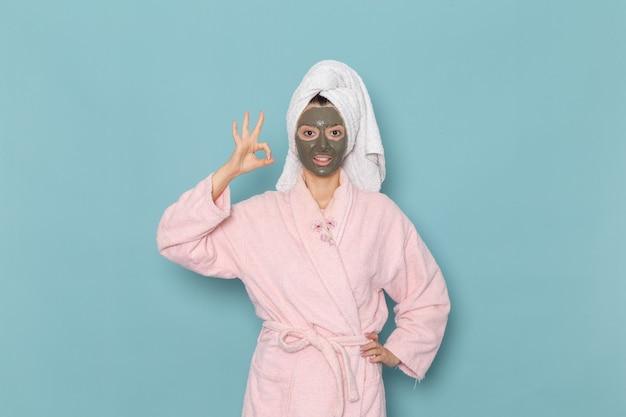Mulher jovem com roupão rosa após o banho com máscara na parede azul beleza água creme autocuidado chuveiro banheiro