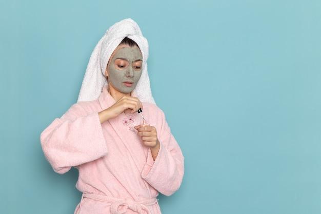 Mulher jovem com roupão rosa após o banho segurando esmalte na parede azul beleza água creme autocuidado chuveiro