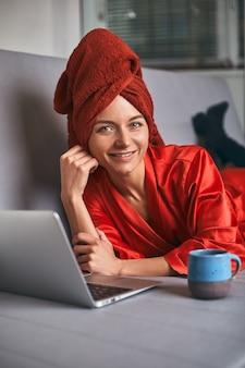 Mulher jovem com roupão vermelho e toalha vermelha na cabeça está de pé na cozinha perto da mesa, bebendo café e usando o laptop